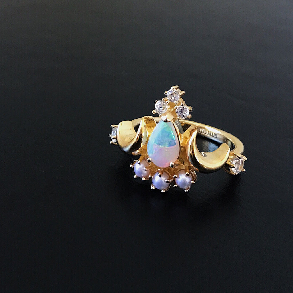 rainbow opal ring with Australian white opal, pearls and sparkling diamonds in a beautiful heritage vintage cocktail ring design in gold - displayed against a black background that really brings out the beautiful rainbow iridescent colours of the opal. Women's jewellery trend.
