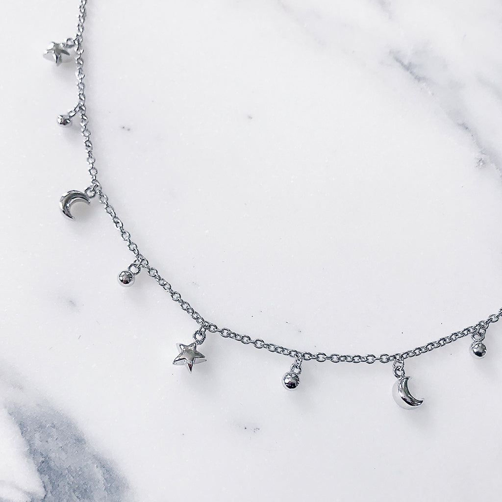 Star moon crescent charms hanging off a fine chain bracelet in silver, so moody and romantic in a beautiful jewelry display