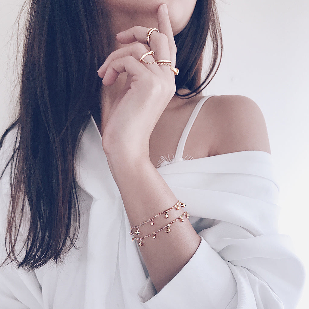 Star moon fine bracelets in 14k gold vermeil layered and worn with beautiful stacking gold chain rings in a sensual, modern and effortless way. womens fine jewellery and bracelets in gold