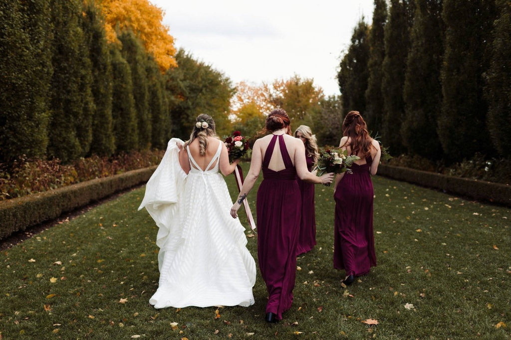 A bride and her bridal party who are wearing floor length burgundy bridesmaids dresses.