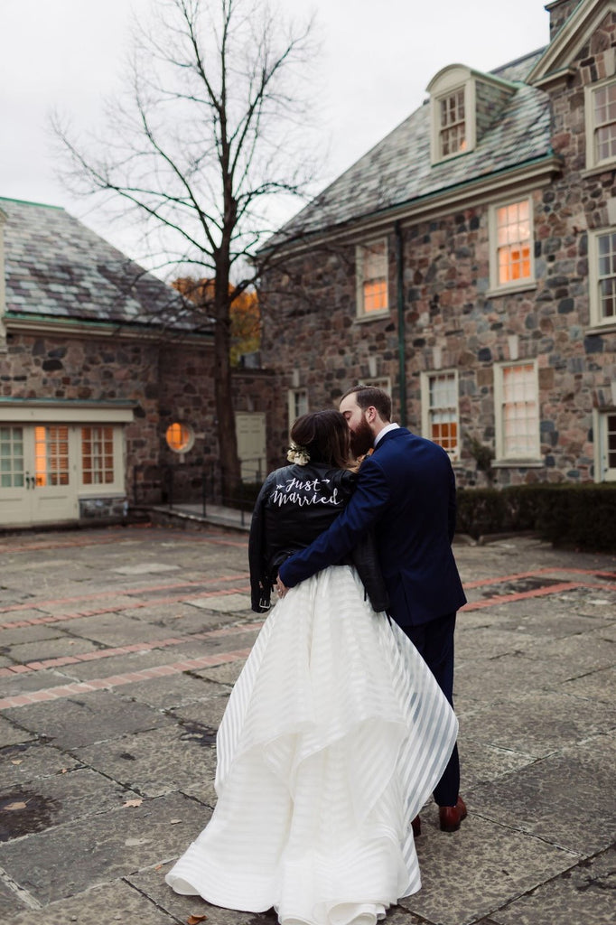 A bride and groom kiss, the bride is wearing #TheJustMarriedJacket.