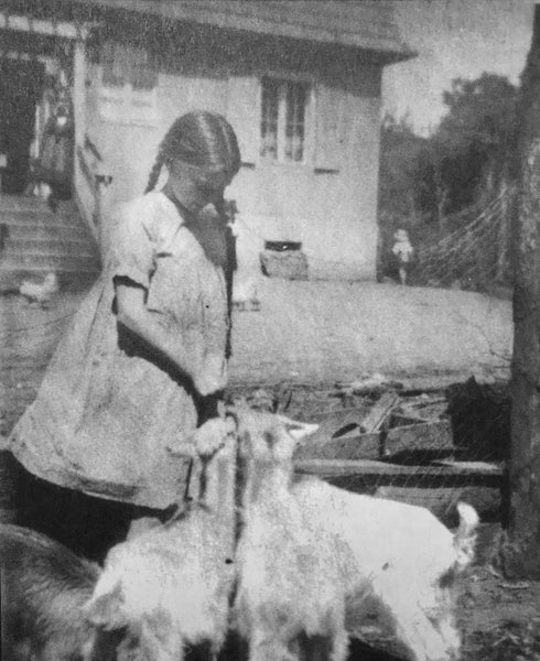 Gisela von Davidson feeding the goats in front of the Blisendorf farmhouse