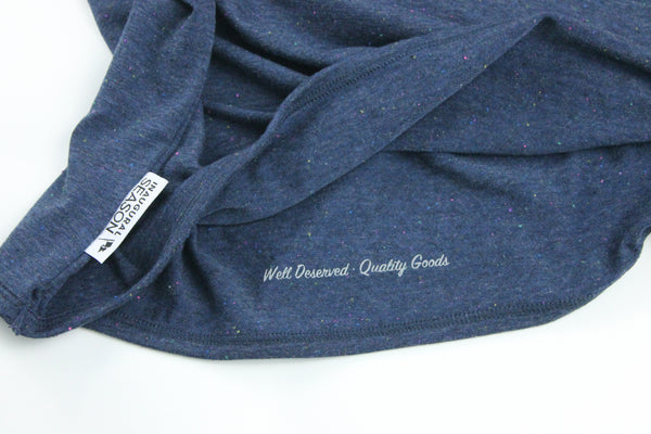 A premium, unisex t-shirt made of blue cotton with a woven tag.