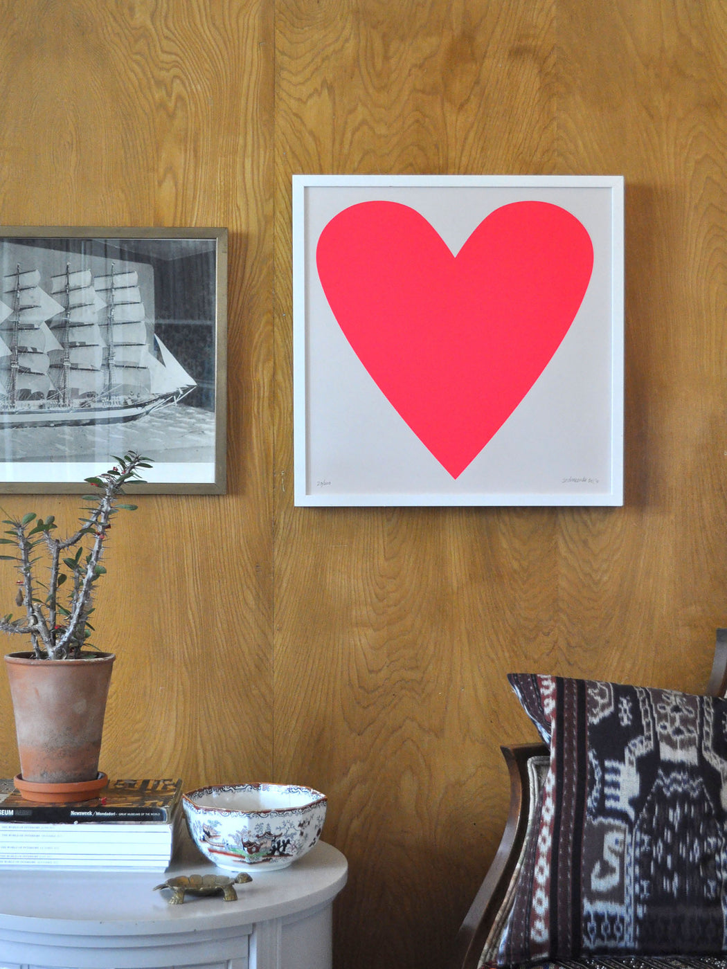 Styled shot of Banquet Workshop's iconic neon red heart with a tall ship and ikat.