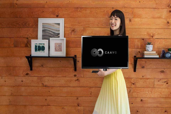 Marie Kondo posing in front of a wooden background while holding a television with the Caavo logo displayed