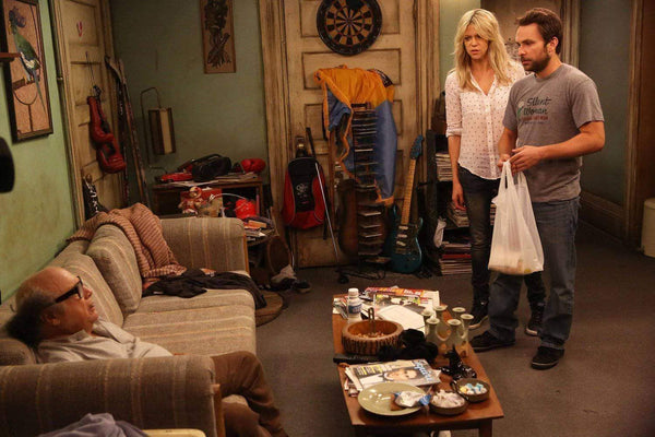 Sweet Dee, Charlie, and Frank starting at each other in Charlie's messy apartment from It's Always Sunny in Philadelphia