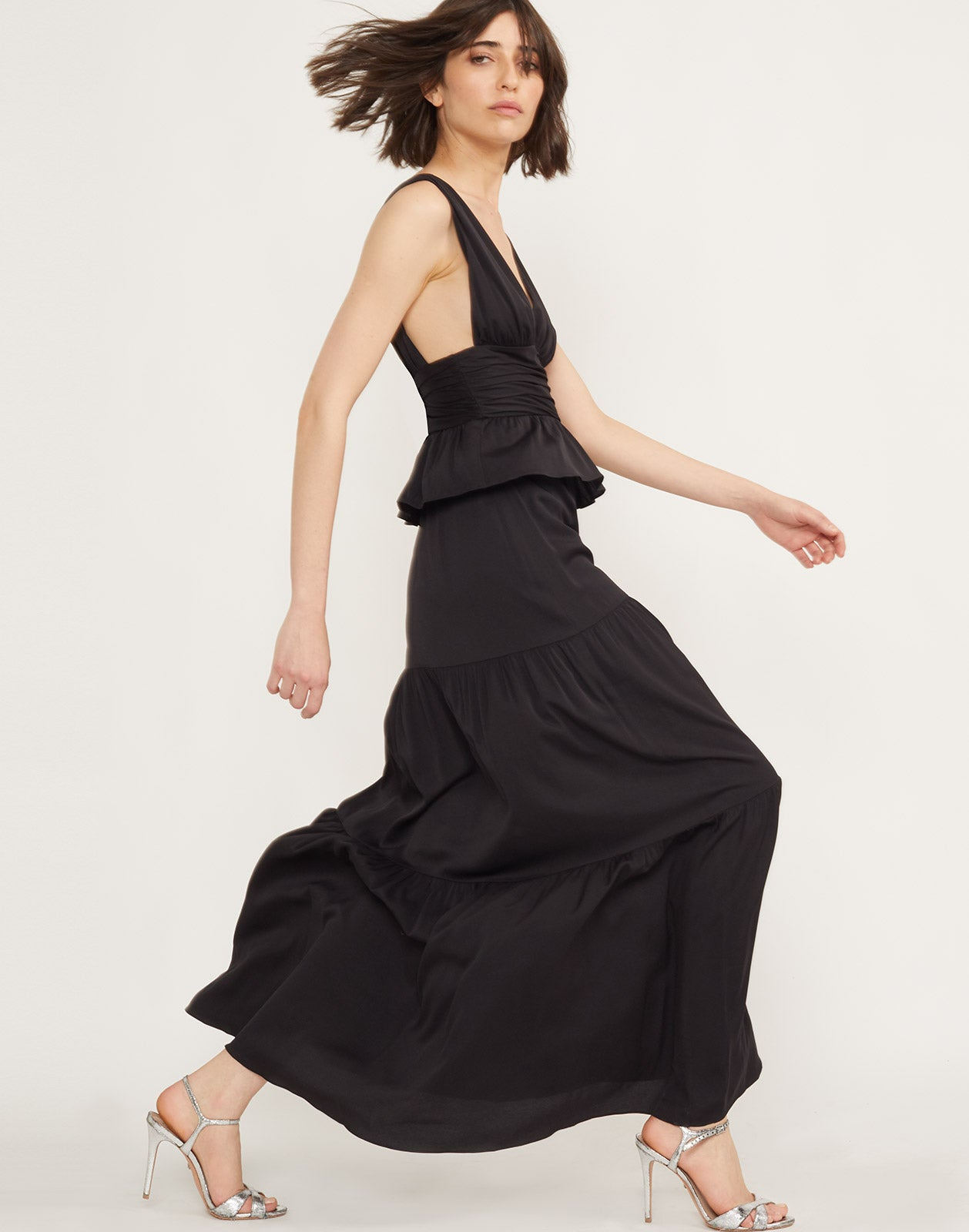Full side view of model wearing Zadie tiered maxi dress in black.