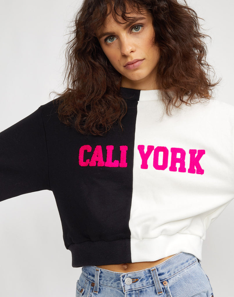Close view of the half black half white CaliYork sweatshirt with hot pink lettering.