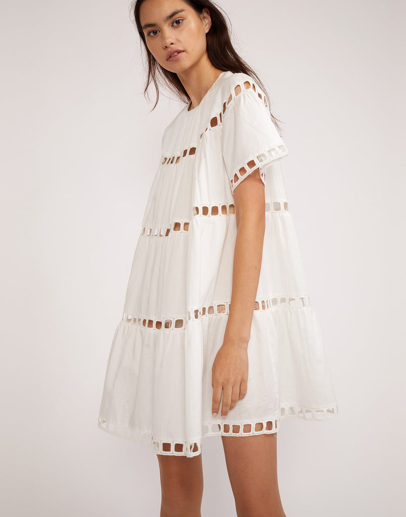 Close side view of the white polished cotton eyelet dress.