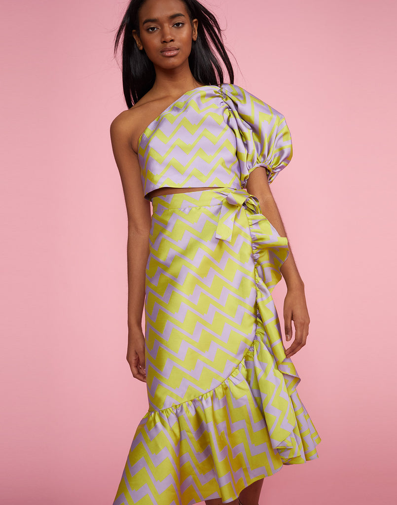 Close front view of the Evanston Brocade Zig Zag Skirt in lavender and lime with ruffles along the bottom and side
