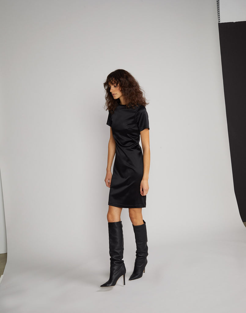 Side view of model wearing Lake Shore stretch satin t-shirt dress in black.