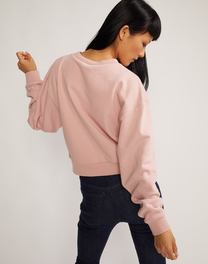 Back view of model wearing embroidered crop role model sweatshirt.