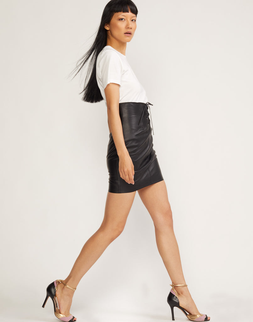 Side view of model walking black lamb leather lace front skirt.