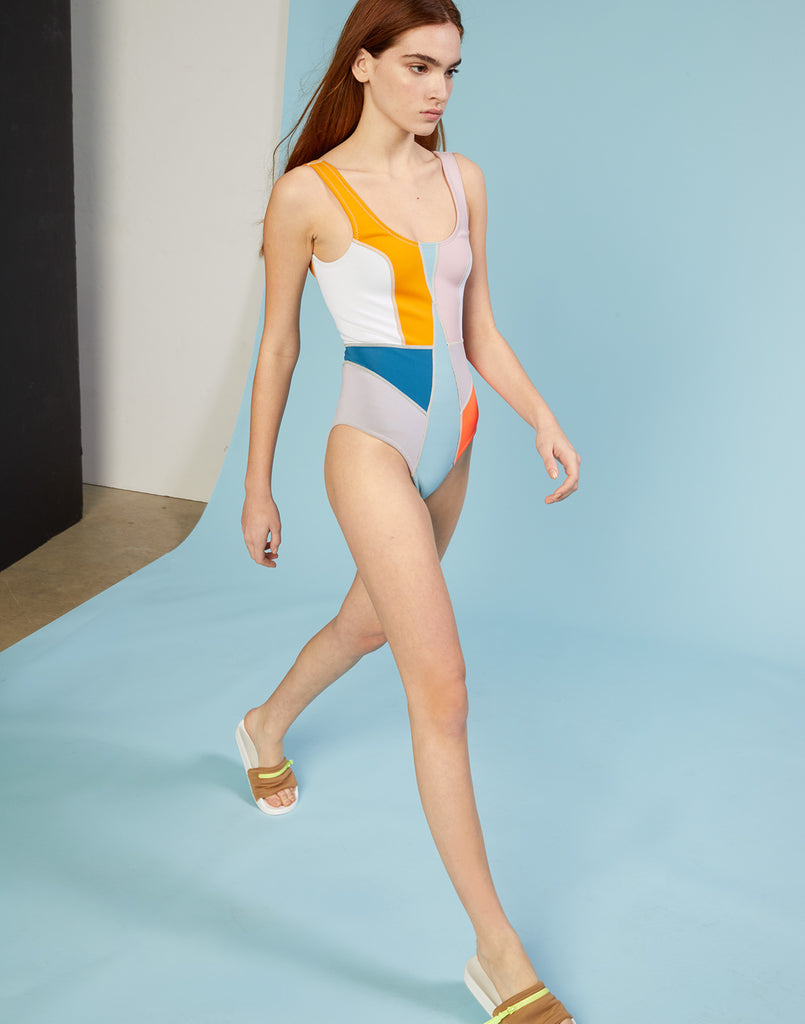 Side view of model walking in multi-color asymmetrical colorblock swimsuit.