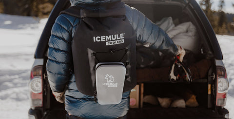 A person carries their IceMule cooler as they prep for an adventure.