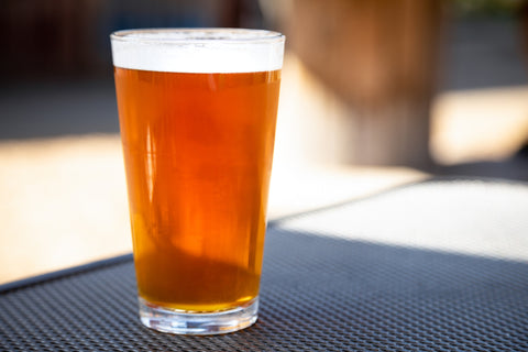 A glass of beer sits on a table in the sun.