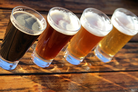 A flight of beers sits on a wooden table.