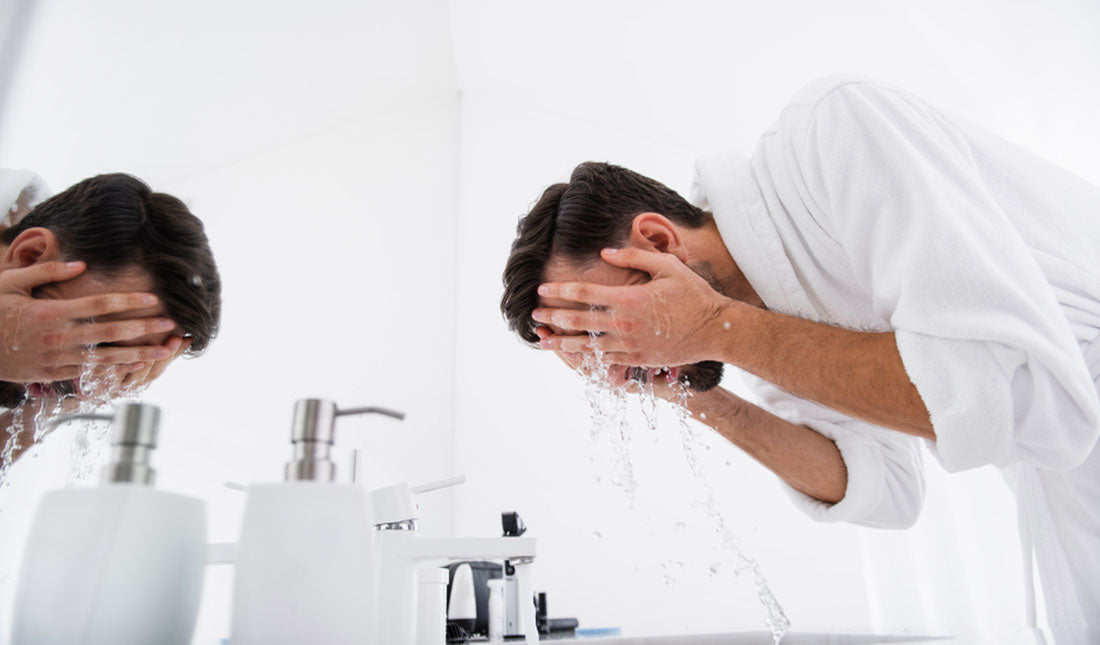 man bending to wash face