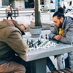 Old and young man playing chess
