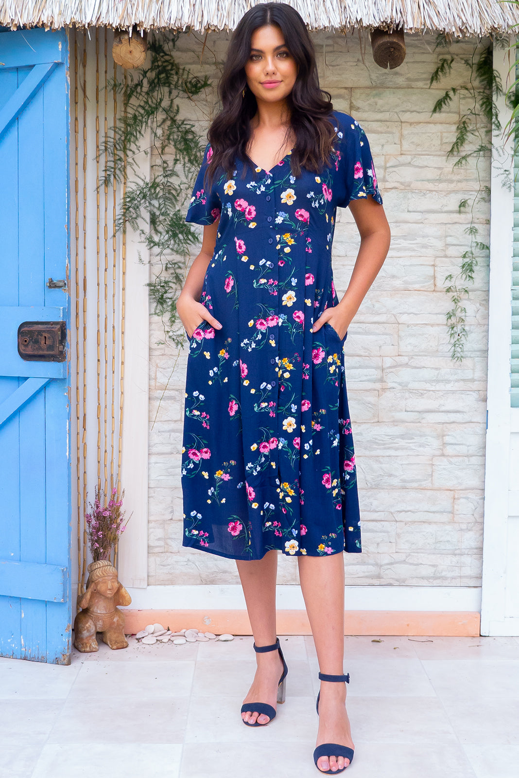 Faithful Chelsea Navy Midi dress features a button front, soft petal sleeve and deep side pockets it is made in a crinkled woven rayon and comes in a bright navy based floral print