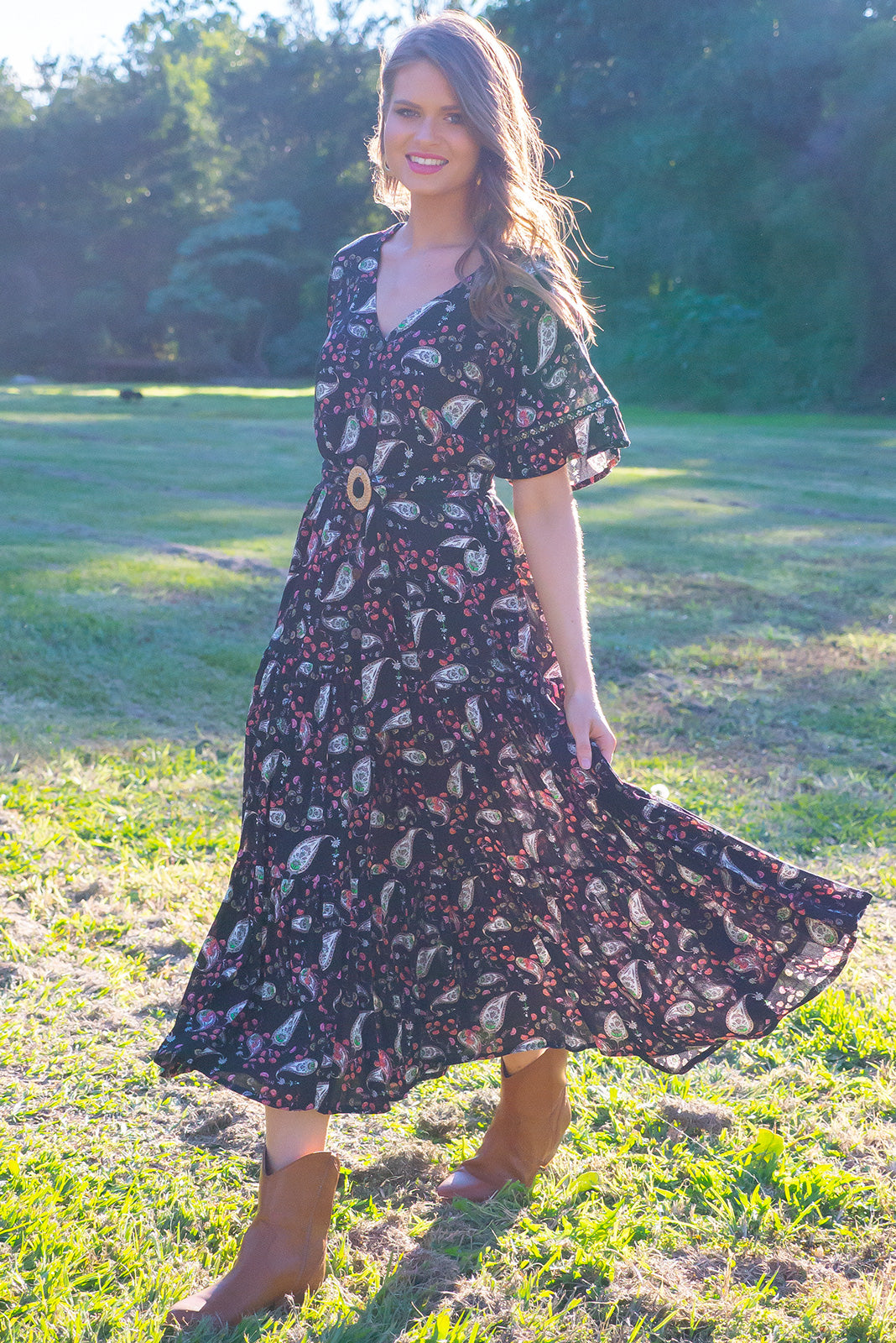 Lucinda Paisley Noir Maxi Dress features a frilled drop waist, button front, soft frill sleeves and a feature rattan buck belt the fabric is a soft crinkle textured woven 100% rayon in a delicate paisley print on a black base