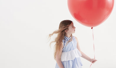 Girl with a red balloon wearing a ruffled dress as an example of trends in children's clothing