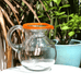 CLEAR GLASS ROUND MEXICAN JUG WITH ORANGE RIM OUTSIDE