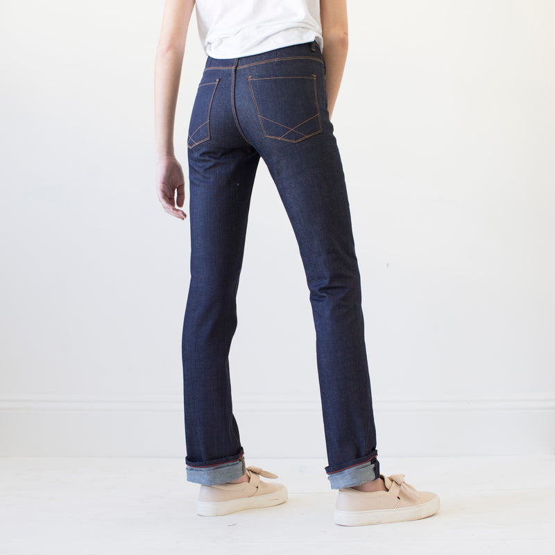 angle: indigo  A model wears Raleigh Denim Workshop Madison high-rise straight leg raw dark jeans, back view