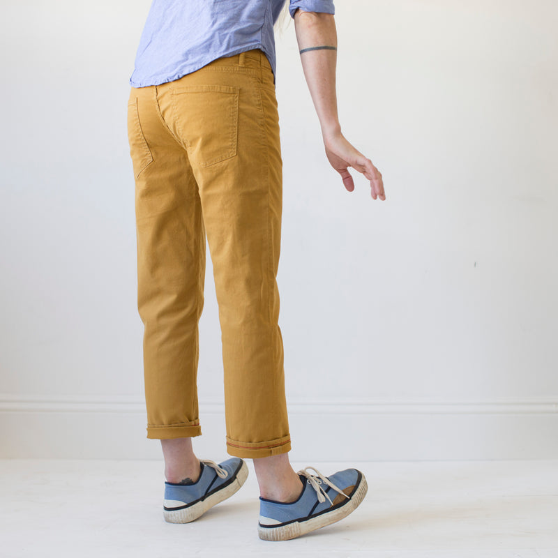 angle hover: turmeric  A model wears Raleigh Denim Workshop women's pants in the Gates fit in turmeric yellow, back side