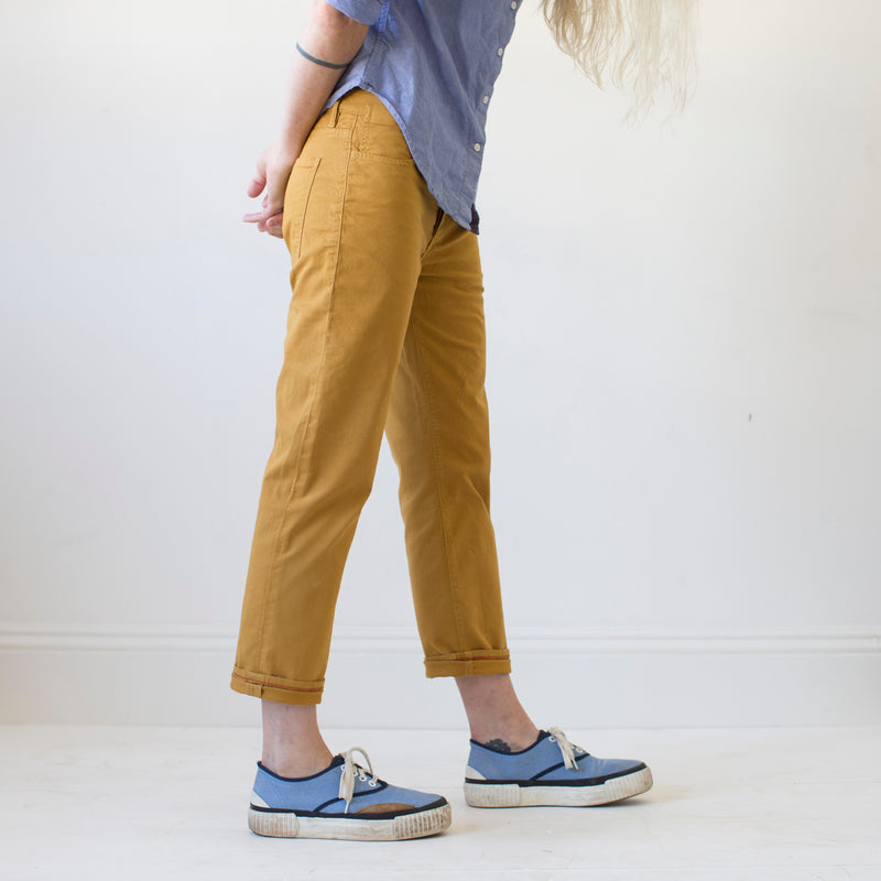 angle: turmeric  A model wears Raleigh Denim Workshop women's pants in the Gates fit in turmeric yellow, side