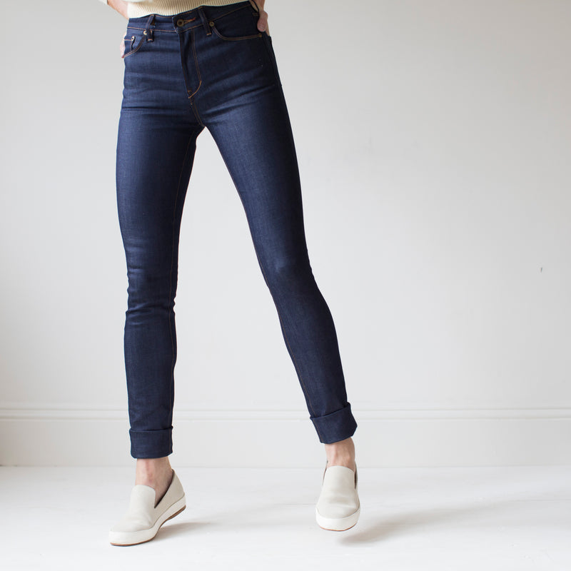 angle: indigo  A model wears Raleigh Denim Workshop Haywood high-rise skinny jeans in dark blue, front view