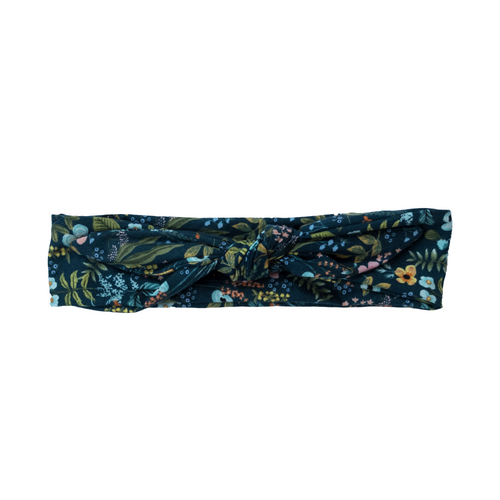 Overview of dark blue cotton headband with light blue, green, pink, and yellow floral detail, tied into a bandanna style knot at center . Stylish headache free head wrap. 90s style headband. Natural hair head wrap. 50s and 60s, classic, rockabilly, pinup style, adjustable bandanna. Painless hair accessories. Bohemian, vintage, punk rock, classic, old Hollywood head wrap. Sculptural, adjustable hair accessories. Cute, comfortable bandanna in dark floral print. Casual headband.