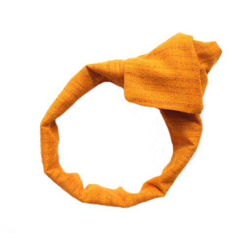 Overview of Bright Marigold Cotton Khadi Wide Wire-Framed Headband tied into rosette. Everyday wear, suitable for all hair types. Adjustable wired head-wrap hair scarf for headache free fit and multi-style wear. Luxury Hair Accessories. Premium Headbands. Wear flat, as a rosette, in a knot, bow, or turban style. Twist around buns for laidback festival hair or to go to the beach. Artisan made, Women Owned Business. Special occasion hair, wear to work, wedding season. Mustard, Gold, Yellow, Turmeric.
