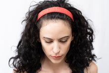 "Woman with dark curly hair, wearing ""Living Coral"" Mini Wire-Framed Headband in front of white background. Pink Headbands, Beachy Hair, Vacation Hair Accessories, Packable Hair Accessories, Resort Hair, Suitable For All Hair Types, Cotton Khadi, Women-Owned, Artisan hair accessories, Luxury Headbands, Premium Headbands."
