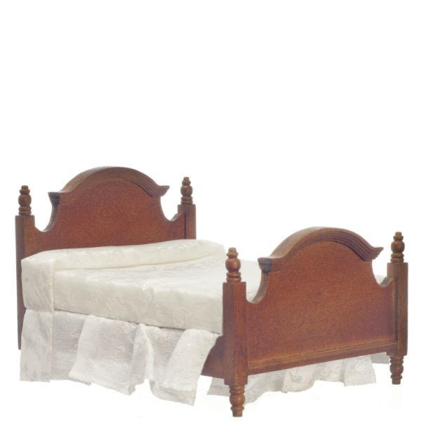 A dollhouse furniture walnut double bed with white mattress and dust ruffle.
