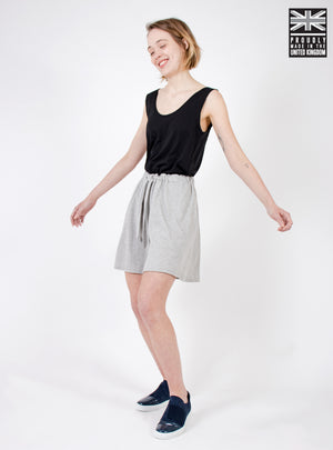 Woman wearing culotte style organic cotton jersey shorts with elasticated waist and pockets. Sustainable fashion style, made ethically in the UK.