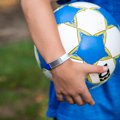 Boy with soccer ball wearing blue ROAD iD Stretch