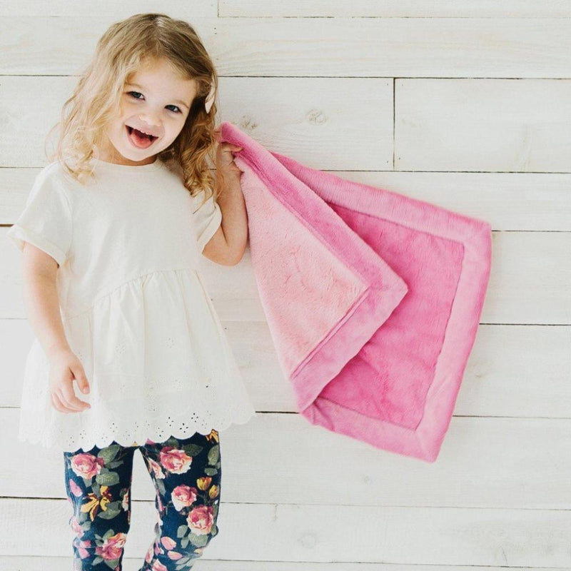 Toddler holds plush blanket for girls featuring a fun combo of light and deep pinks.
