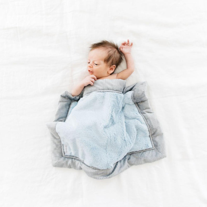 Newborn sleeping underneath a plush light blue baby blanket.