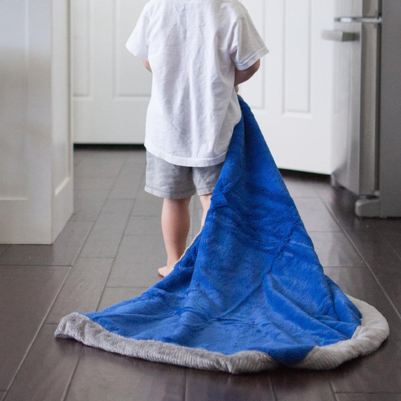 Young boy pulls his bright royal blue plush kid throw behind him.