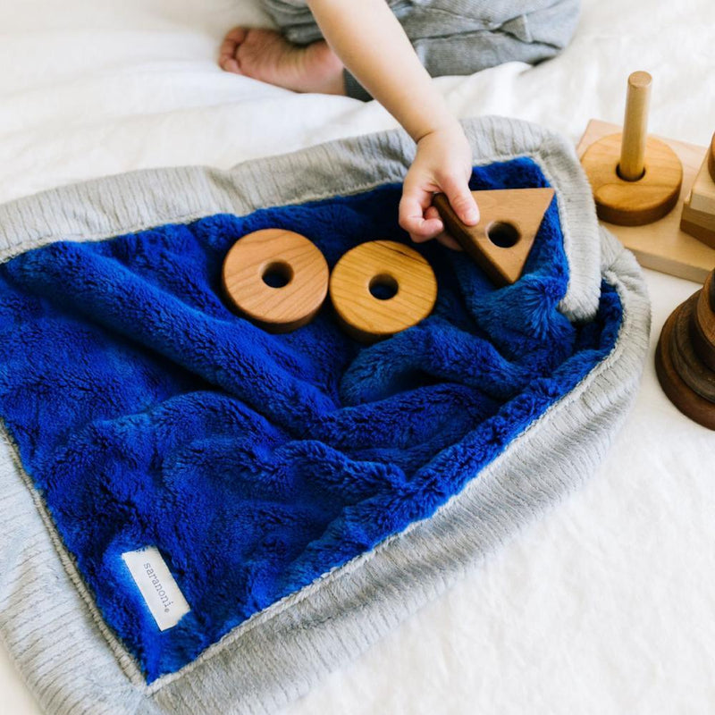 Toddler plays with wood blocks on a plush royal blue baby boy blanket.