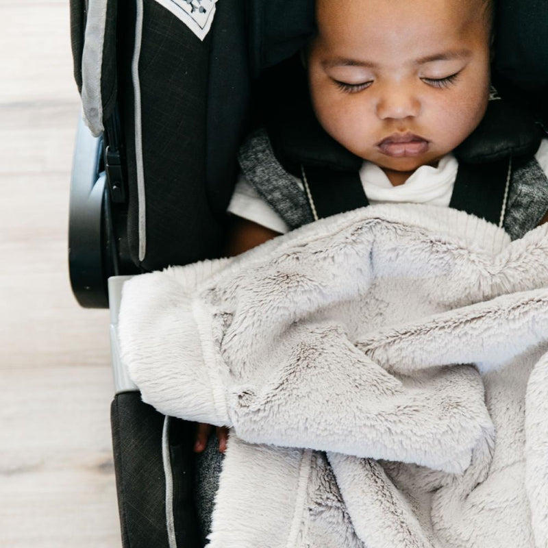 Baby boy snuggled under a mini, neutral colored car seat blanket.