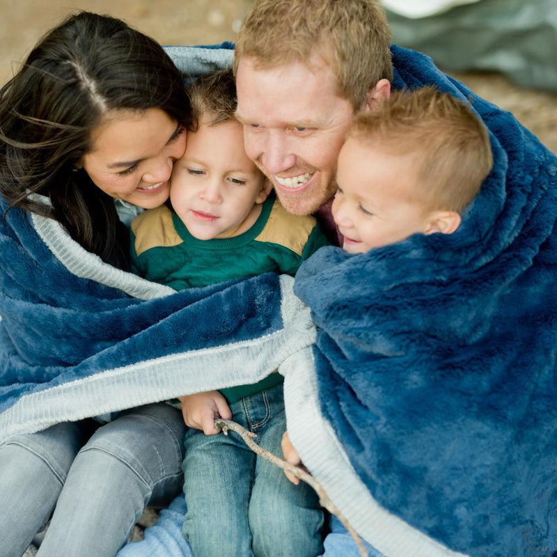 Young family wrapping up in an extra large Navy blue plush blanket while camping.