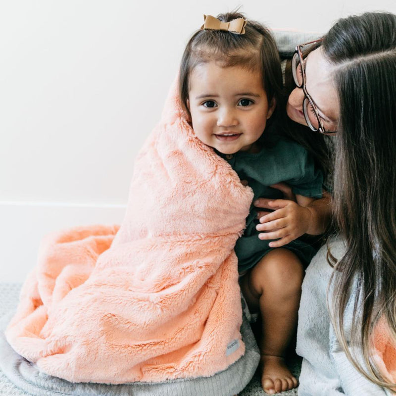 Mother wraps toddler in a luxurious plush melon gray throw for kids.