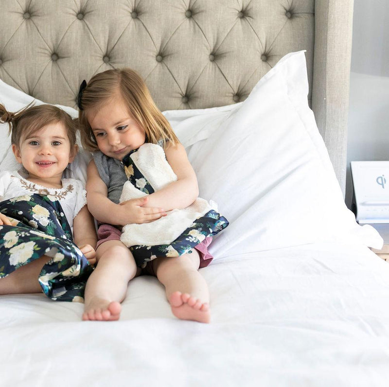 Two cute girls sit on the bed with their ivory floral plush baby blankets.