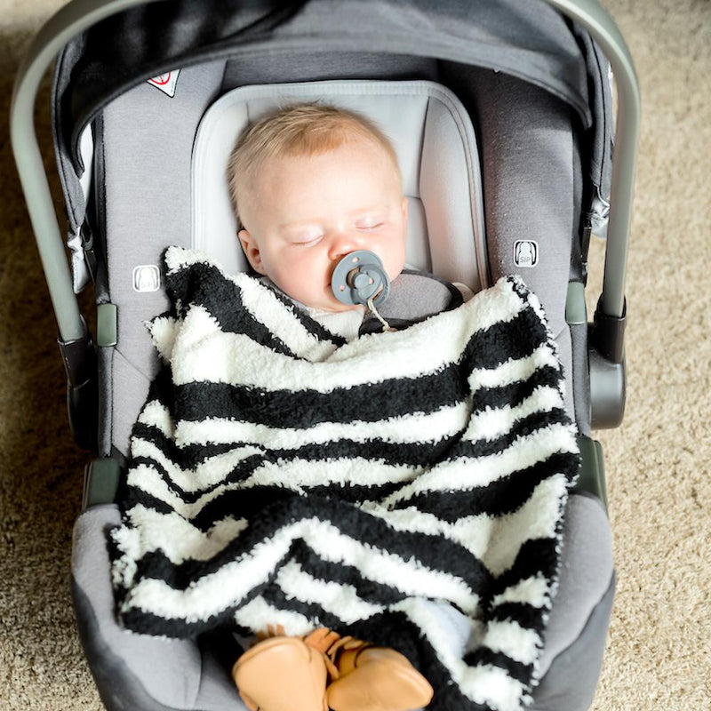 Baby boy naps with a black and white striped mini baby blanket.