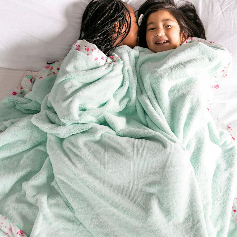 Young girls snuggle under a warm mint plush blanket with a silky satin border
