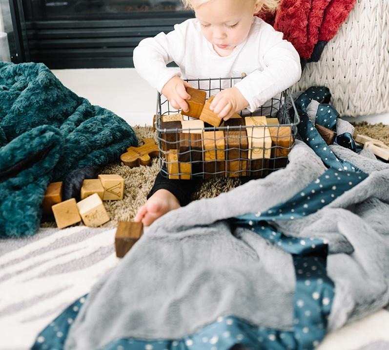 Toddler plays with blocks next to an oversized gray lush blanket with a navy star satin border.