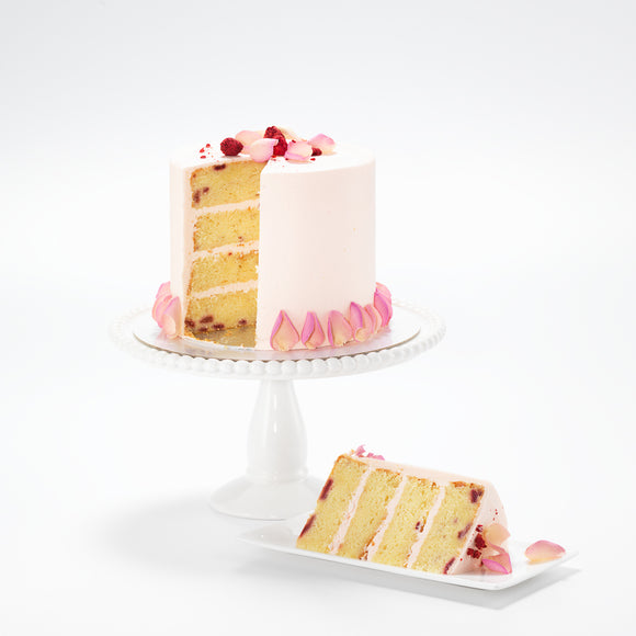 A delicately decorated raspberry and rose cake. Its rich, raspberry sponge is perfectly complimented by subtle, rose buttercream.  While the rose buttercream icing is graced with edible candy pink rose petals and a sprinkle of freeze-dried raspberries.