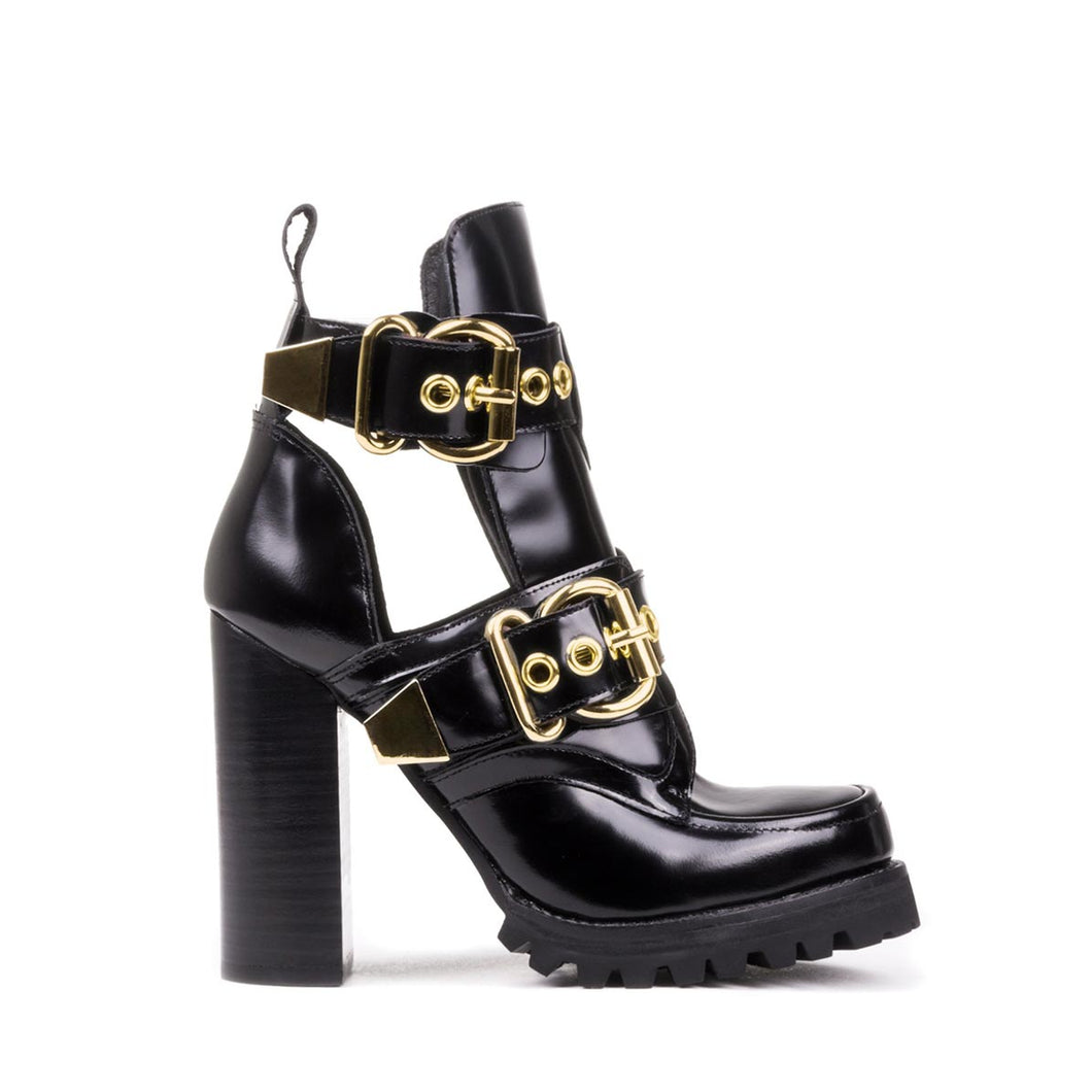Golden buckles over side cutouts accentuate the moccasin seam shaft on the Jeffrey Campbell Craven in black high shine calf leather. The lugged sole adds a moto edge to this lofty block heeled bootie. Free National Shipping. Afterpay and ziPpay available.